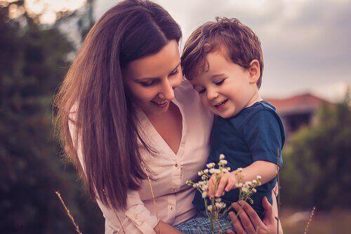 Madre con bambino in braccio che guarda un fiore