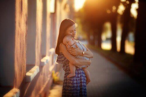 Madre con figlio in braccio per strada