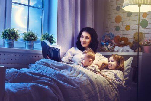 Madre nel letto con bambini che legge favola