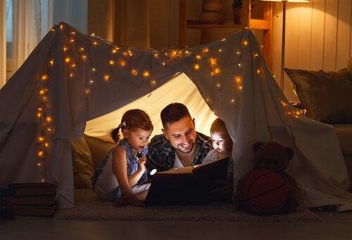 Padre che legge racconto a bambini nella tenda