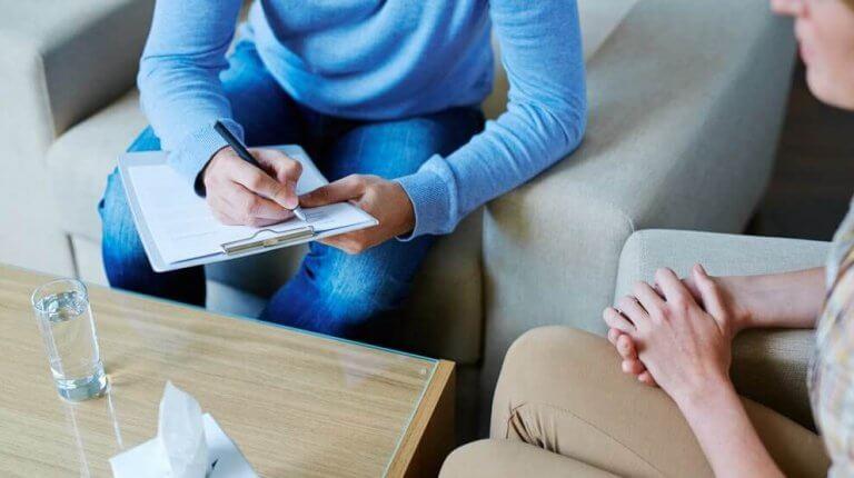Psicologo che prende appunti su paziente