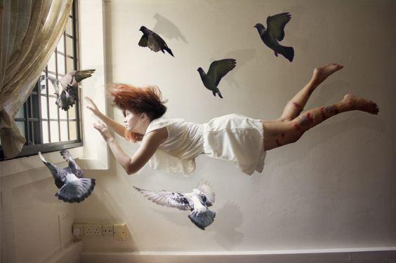 Ragazza fluttua in aria circondata da colombi
