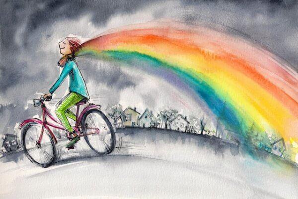 Ragazza in bicicletta con sciarpa arcobaleno