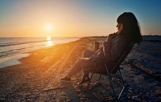 Donna che si rilassa in spiaggia durante il tramonto