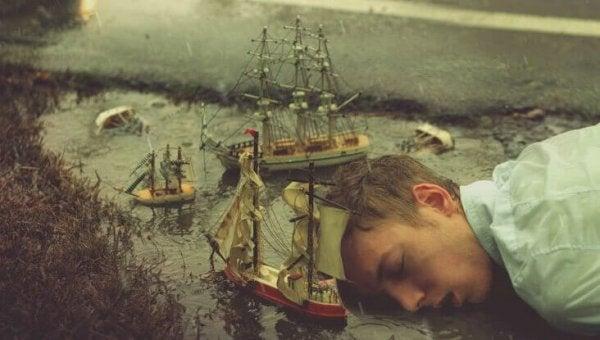 Ragazzo che dorme su una pozzanghera con barche