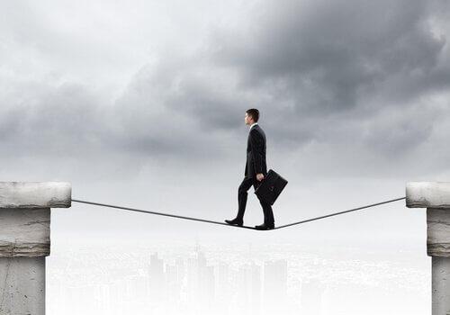 Uomo cammina su una corda sospesa a rappresentare gli atteggiamenti che non esprimono paura ma lo fanno