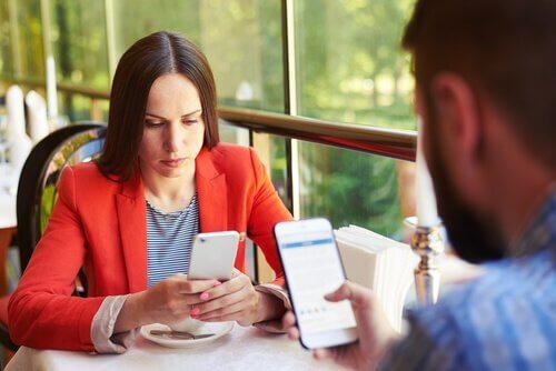 Coppia seduta a tavola con cellulari in mano