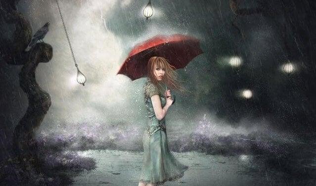 Donna sotto la pioggia con ombrello rosso