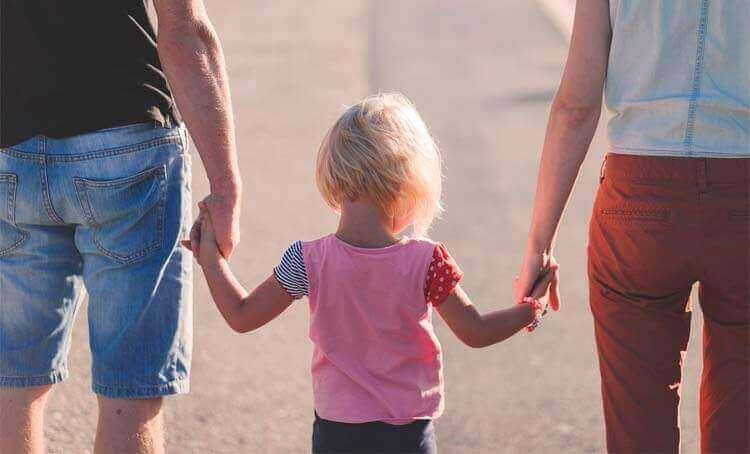 Genitori tengono per mano la figlia