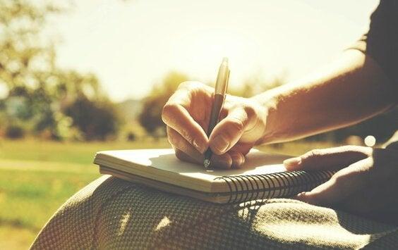 Mano con penna e quaderno