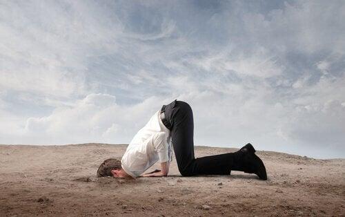 Uomo con la testa dentro la sabbia