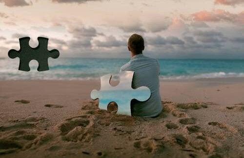uomo davanti al mare e pezzo di puzzle mancante
