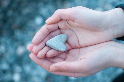 Cuoricino di pietra tenuti da mani giunte