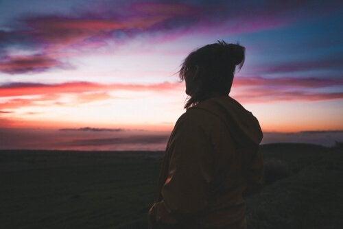 Donna osserva tramonto mentre cerca la sua motivazione intrinseca