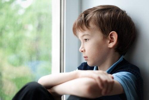 Bambino guarda seduto oltre la finestra