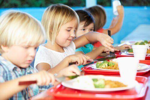 Bambini che mangiano le verdure nella mensa scolastica