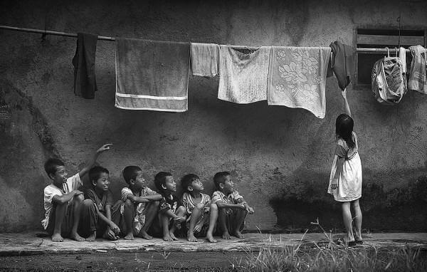 Bambini seduti guardano bambina stendere i panni