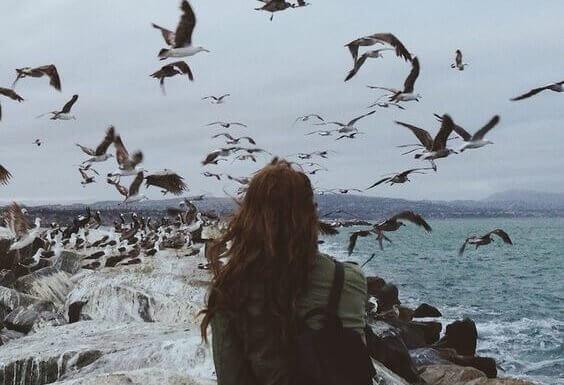 Donna al mare osserva gli uccelli