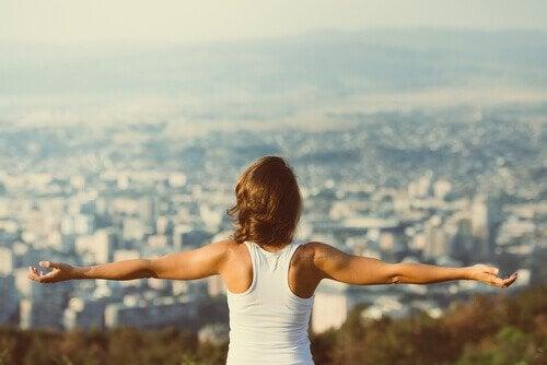 Donna con braccia aperte di fronte a panorama cittadino
