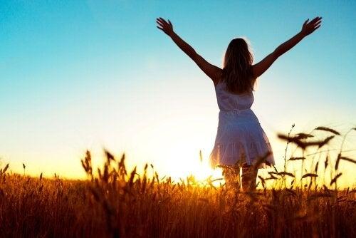 Donna con le braccia alzate in un campo di grano