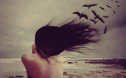 Donna in riva al mare con uccelli neri