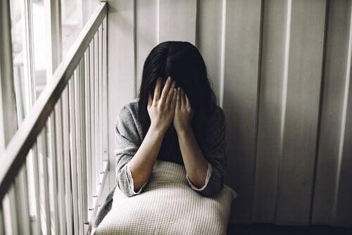 Donna triste che si copre il viso