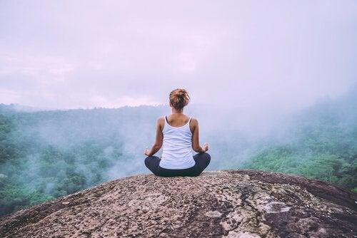 Ragazza medita in montagna