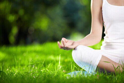 Ragazza medita seduta sul prato