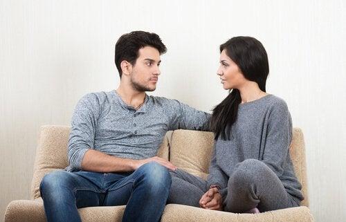 Coppia seduta sul divano parla delle aspettative