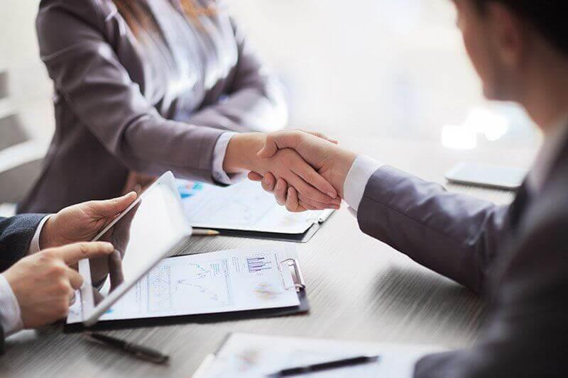 Mani che si stringono al colloquio di lavoro
