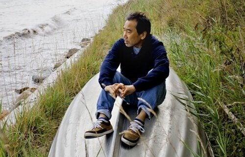 Murakami seduto sulla sponda di un fiume