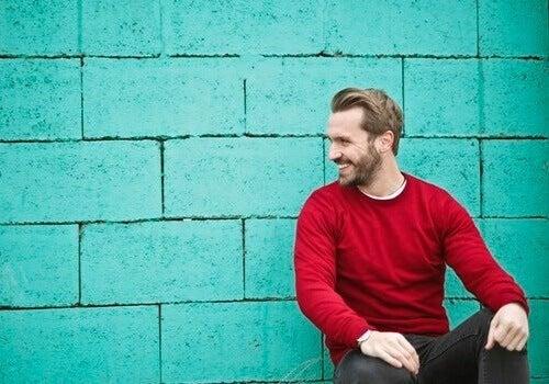Uomo ride davanti a un muro blu