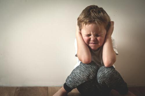 Bambino con mani sulle orecchie
