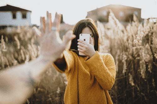 Persone che battono il cinque con il cellulare davanti agli occhi