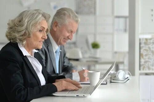 Coppia di anziani lavora al computer