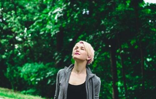 Donna con gli occhi chiusi sotto gli alberi