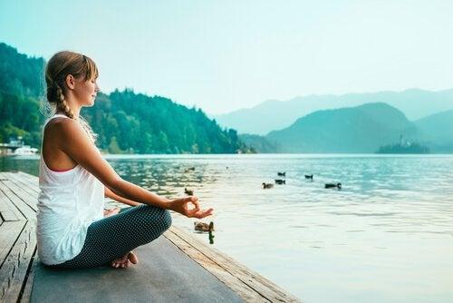 Donna seduta in meditazione davanti a un lago