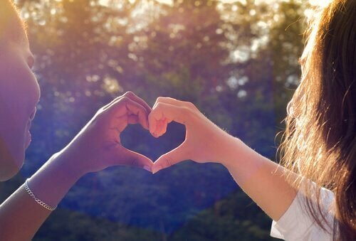 Due amiche formano un cuore con le mani