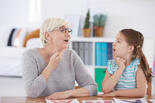 Logopedista che aiuta una bambina a parlare