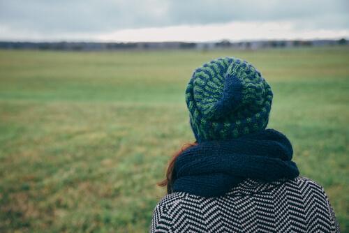 Ragazza di spalle con berretto e sciarpa