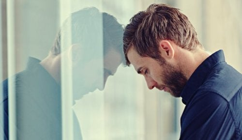 Uomo con testa appoggiata alla finestra
