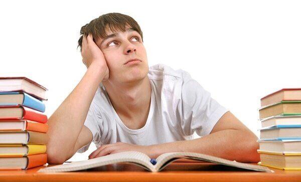 Adolescente distratto tra pile di libri