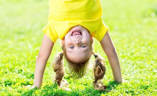 Bambina che fa la verticale sull'erba
