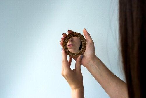Donna con piccolo specchio nelle mani