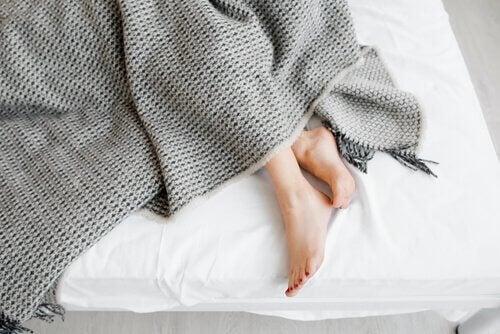 Piedi di una donna spuntano dalle coperte