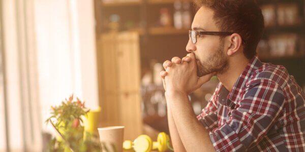 Ragazzo con gli occhiali seduto a pensare