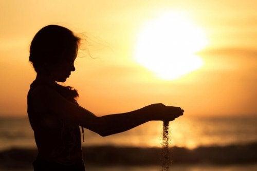 Bambina sabbia tramonto
