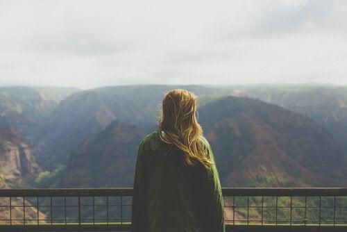 Donna di spalle osserva un panorama montano