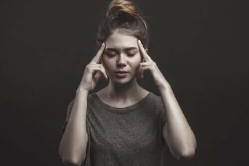 Una donna tiene le mani sulle tempie e gli occhi chiusi