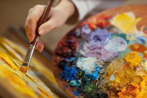Mano con pennello e tavolozza di colori